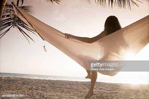 Young woman sitting in hammock, rear view