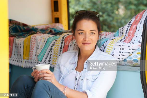 Young woman sitting in her camper van holding a mug of tea