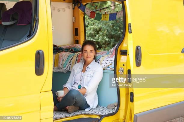 Young woman sitting in her camper van