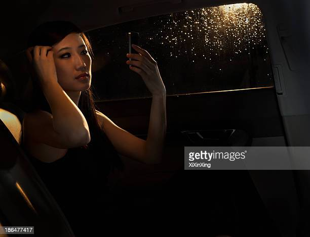 Young woman sitting in her car and checking her hair in the phone before going out on a rainy night in Beijing