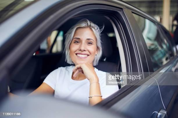 young woman sitting in her car - auto stock-fotos und bilder