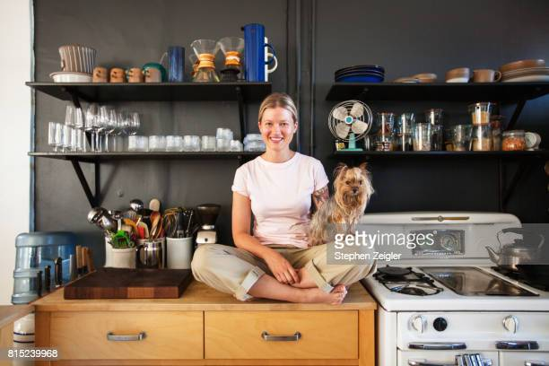 young woman sitting in her kitchen with her dog - one animal stock pictures, royalty-free photos & images