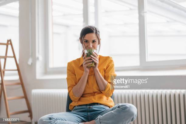 young woman sitting in her new flat drinking tea - tea stock photos and pictures