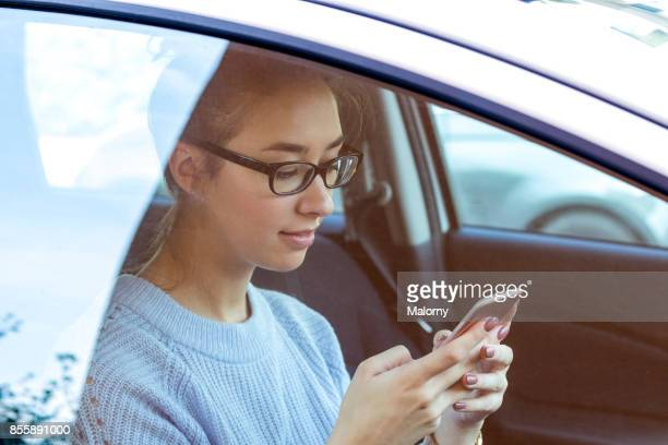 Young woman sitting in her parked car and texting on her smartphone. View through the window.