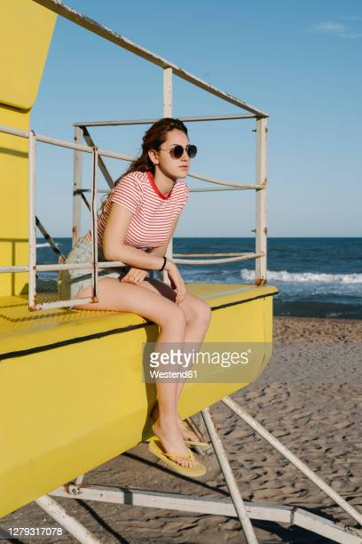 young woman sitting in lifeguard hut on beach during sunny day - cabine de plage photos et images de collection