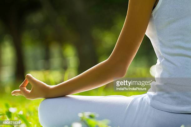 Young woman sitting in lotus position at park