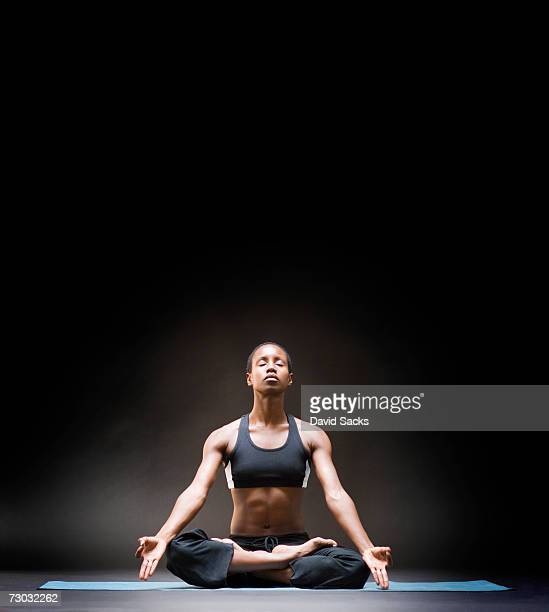 Young woman sitting in lotus position, front view