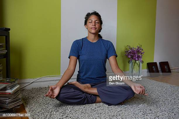 Young woman sitting in lotus position in living room