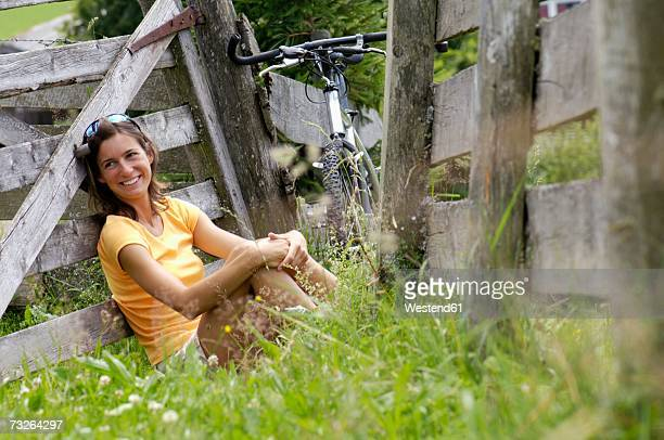 young woman sitting in meadow, leaning on fence