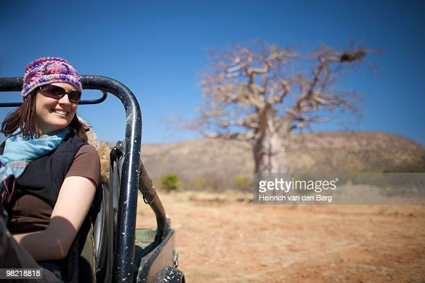 Young woman sitting in motor vehicle with Baobab tree in background, Kunene river area, Kaokoland, N