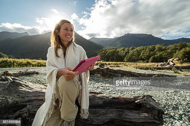 Young woman sitting in nature uses a digital tablet