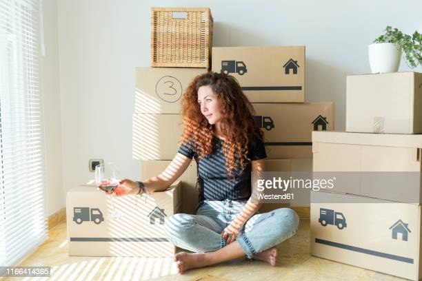 young woman sitting in new home with glass of red wine - indépendance photos et images de collection