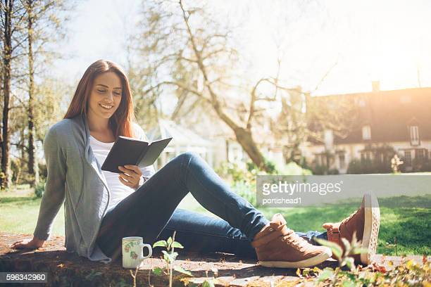 Young woman sitting in park and reading a book