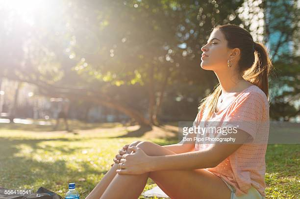 Young woman sitting in park with eyes closed, Manila, Philippines