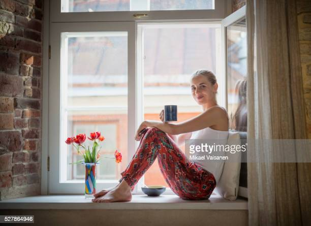 young woman sitting in pyjamas on windowsill - window sill stock pictures, royalty-free photos & images