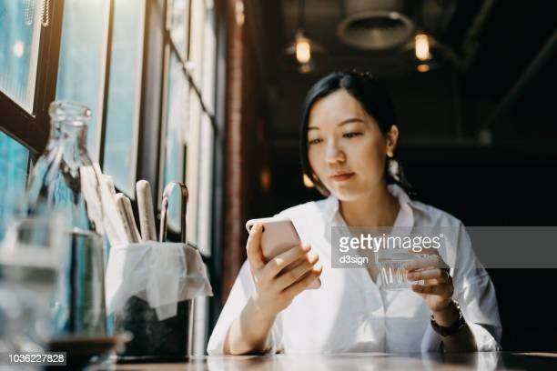 Young woman sitting in restaurant looking at her mobile phone