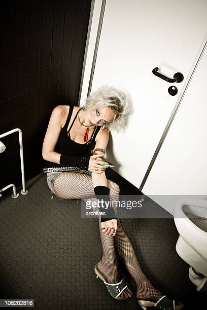 young woman sitting in restroom injecting drugs from needle - shooting up stock pictures, royalty-free photos & images