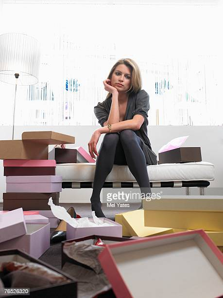 Young woman sitting in shop surrounded by opened shoe boxes