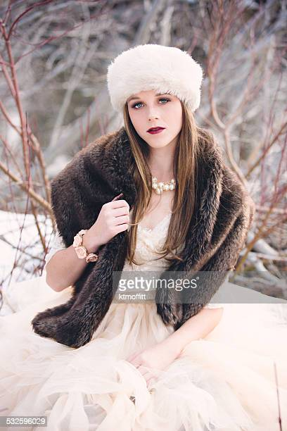 Young Woman Sitting In Snow With Fur Hat