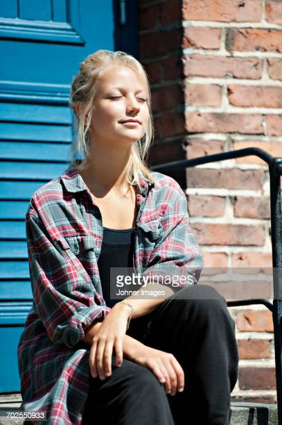 young woman sitting in stairs in front of house - girls sunbathing stock pictures, royalty-free photos & images