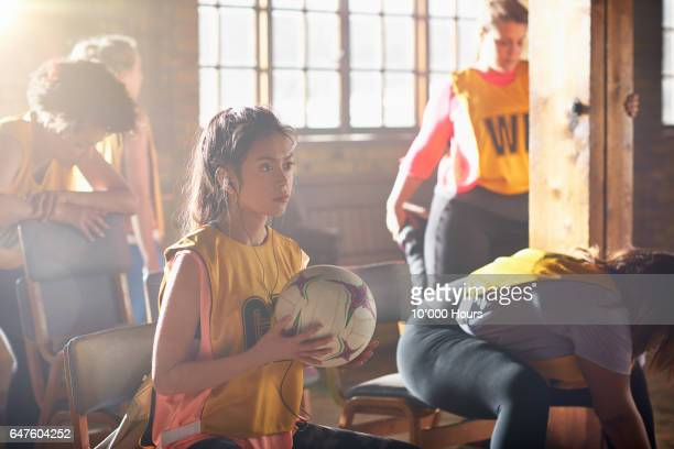 Young woman sitting in sunny gym, holding netball.