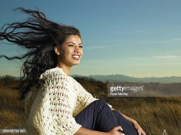 Tailles jeune femme assise sur l'herbe au coucher du soleil, les cheveux