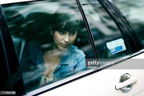 Young woman sitting in taxi cab