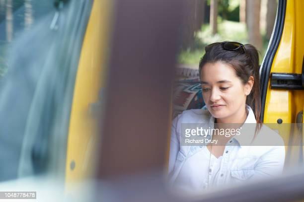 Young woman sitting in the doorway of her camper van