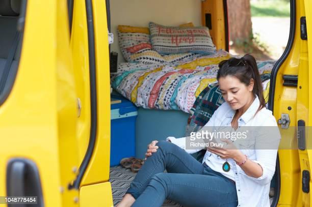 Young woman sitting in the doorway of her camper van using a smart phone