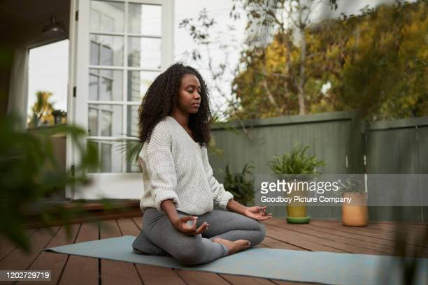 young woman sitting in the lotus pose outside on her patio - body care stock pictures, royalty-free photos & images