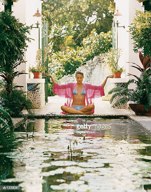 Young Woman Sitting in the Lotus Position at the End of a Pond in a Courtyard