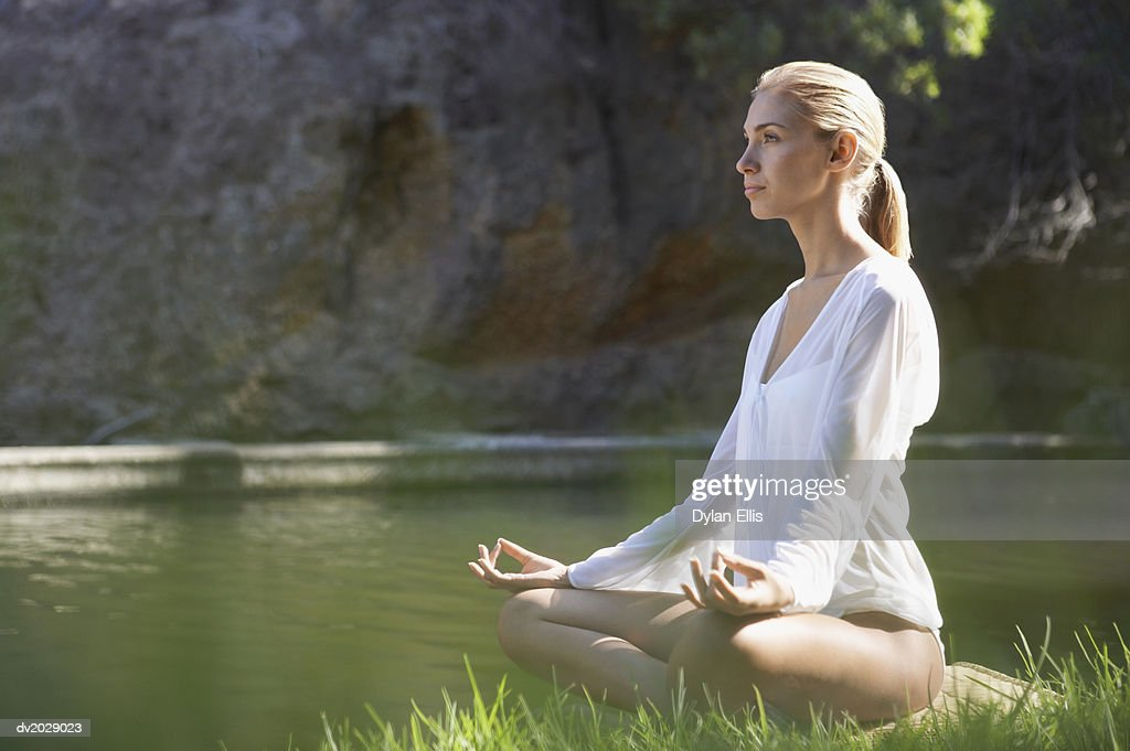 Young Woman Sitting in the Lotus Position by a Lake : Stock Photo