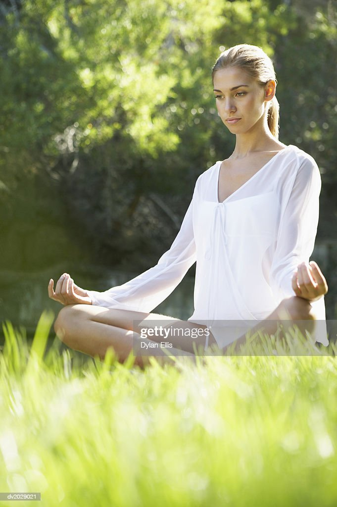 Young Woman Sitting in the Lotus Position on the Grass : Stock Photo