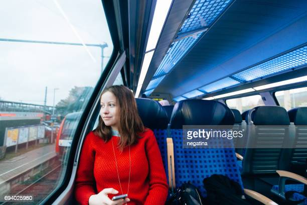 young woman sitting in the train holding her smart phone looking into the window