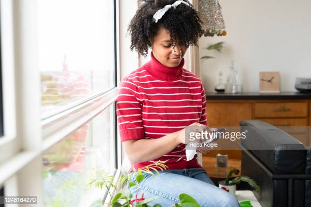 young woman sitting in the window frame. - wet wipe stock pictures, royalty-free photos & images