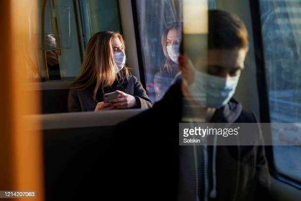young woman sitting in train wearing protective mask, using smartphone - corona virus stock pictures, royalty-free photos & images