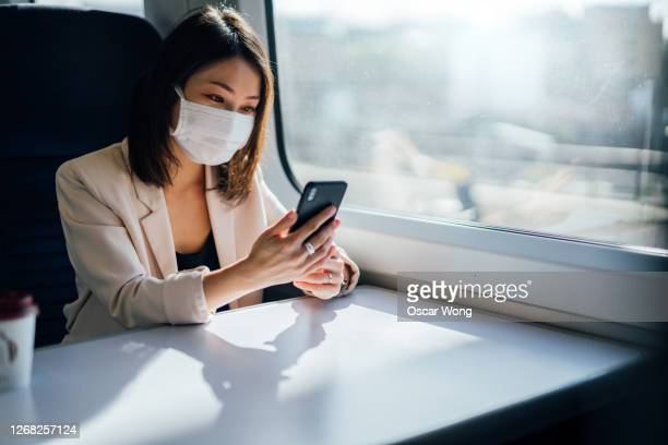 young woman sitting in train wearing protective mask, using smartphone - travel stock pictures, royalty-free photos & images