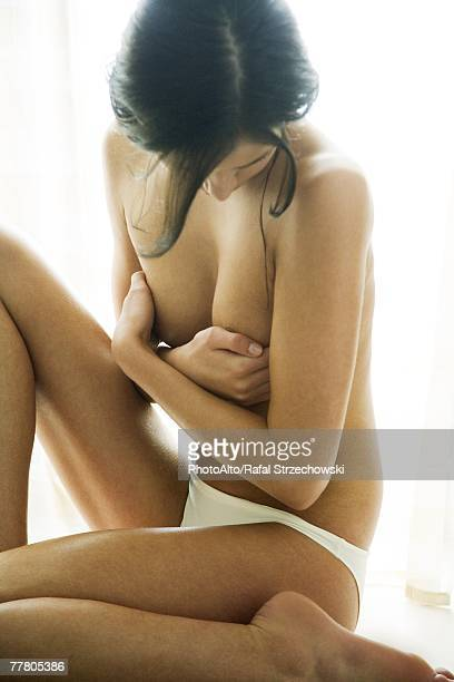 Young woman sitting in underwear, covering chest, looking down