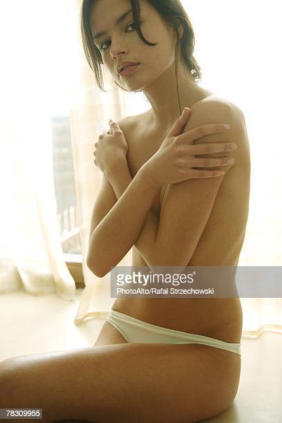 Young woman sitting in underwear, covering chest with arms, looking at camera