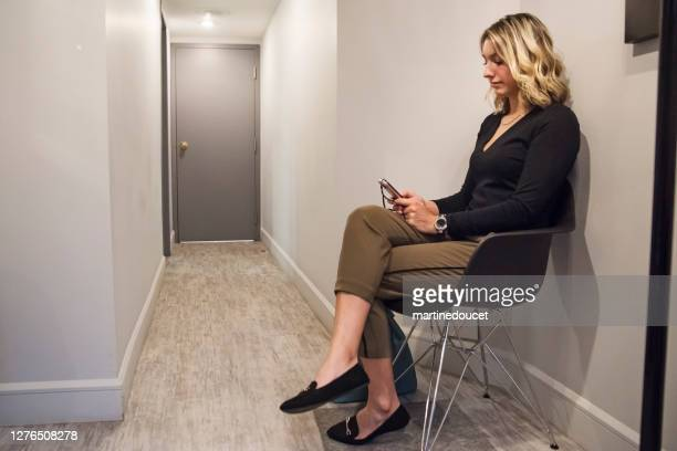 """young woman sitting in waiting room. - """"martine doucet"""" or martinedoucet stock pictures, royalty-free photos & images"""