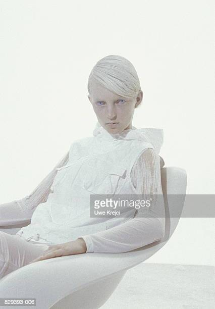 Young woman sitting in white environment, portrait