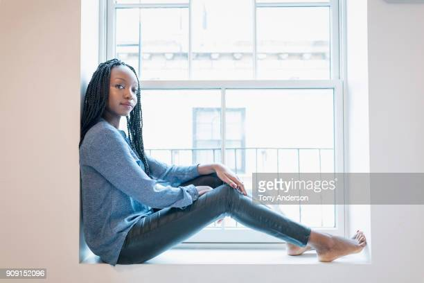 Young woman sitting in window sill at home