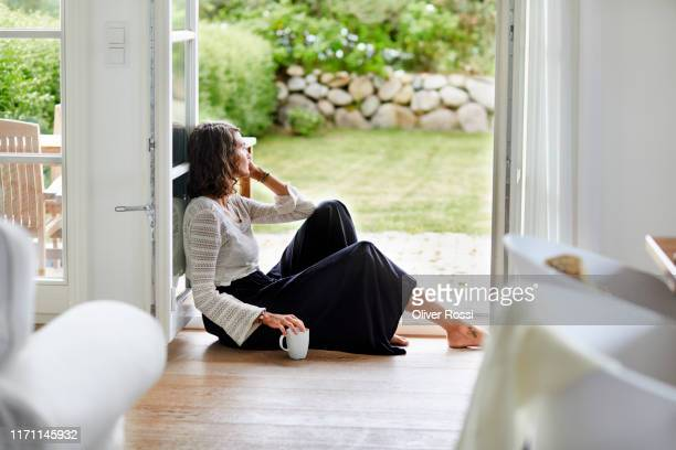 young woman sitting in windowframe looking out - verdriet stockfoto's en -beelden