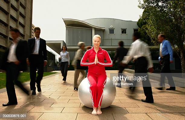 young woman sitting in yoga pose on exercise ball in busy street - hands in her pants fotografías e imágenes de stock