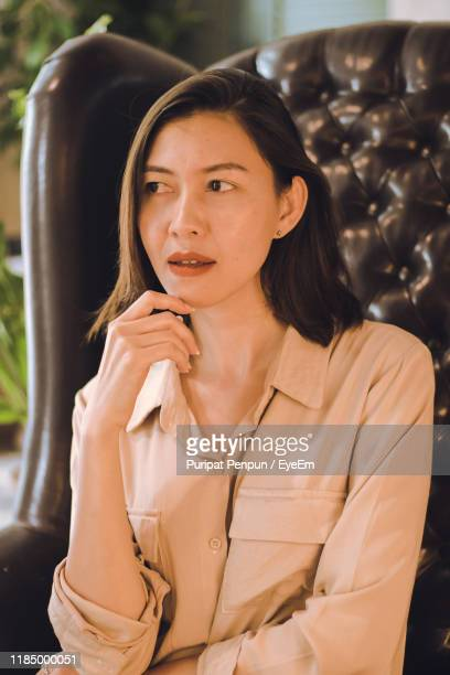 young woman sitting indoors - thai mueang photos et images de collection