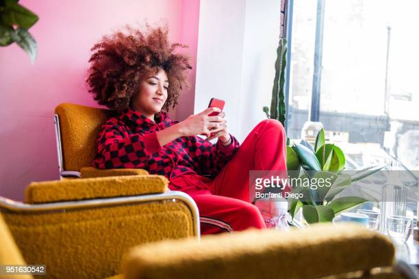young woman sitting indoors, using smartphone - one young woman only stock pictures, royalty-free photos & images