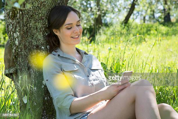 Young woman sitting leaning against tree using smartphone looking down smiling