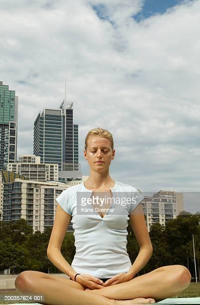 Young woman sitting meditating, low angle