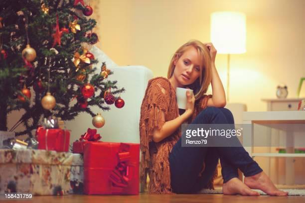 Jeune femme assise près d'un arbre de Noël