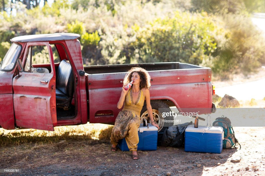 Young Woman Sitting Next To Old Rusty Pick Up Truck Drinking From ...